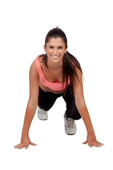 Aantrekkelijk meisje met sportenkleren die opdrukoefening maken die op een witte achtergrond wordt geïsoleerd