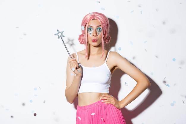 Aantrekkelijk meisje met toverstaf vieren halloween in sprookjeskostuum en roze pruik, koket camera kijken, permanent terwijl confetti vallen.