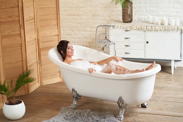 Aantrekkelijk meisje ontspant in de badkamer en rust tegen de achtergrond van een prachtig licht interieur