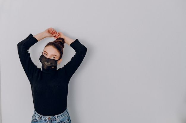 Aantrekkelijk meisje op een lichte muur draagt een medisch masker. gebruik van persoonlijke bescherming. anti-epidemie en bescherming tegen vervuiling van de persoon.