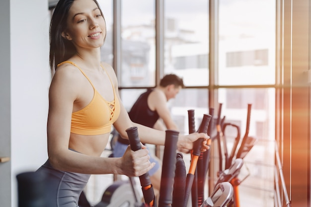 Aantrekkelijk meisje op sportschool op hometrainer, fitness en yoga