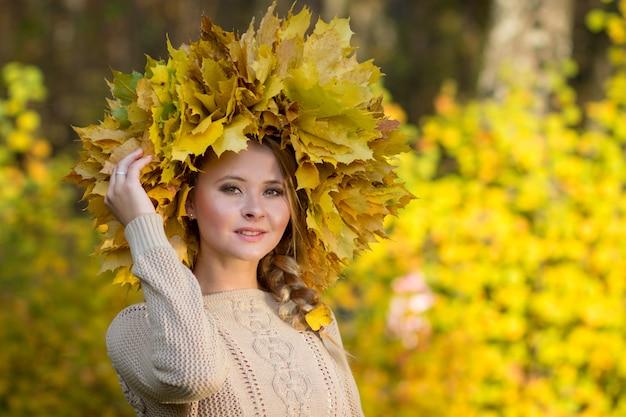 Aantrekkelijk meisje poseren met een krans van bladeren.