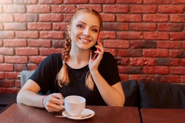 Aantrekkelijk meisje praten over telefoon terwijl het drinken van koffie in gezellig café tegen bakstenen muur