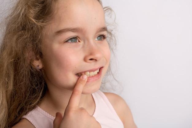 Aantrekkelijk meisje staat op een witte achtergrond, gelukkige uitdrukking op haar gezicht met een mooie glimlach, kinderen scheve tanden, pediatrische tandheelkunde. hoge kwaliteit foto