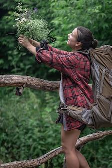 Aantrekkelijk meisje toerist met een grote rugzak voor reizen en met een boeket van wilde bloemen.