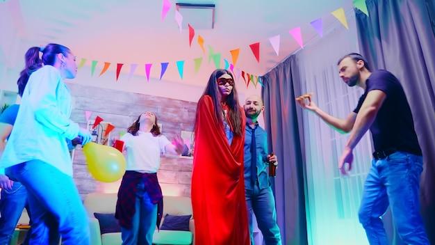 Aantrekkelijk meisje vol opwinding met een rode superheldenpet terwijl ze danst met haar vrienden op een wild collegefeest met neonlichten.