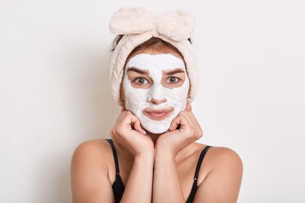 Aantrekkelijk meisje vond acne en deed huidverzorgingsprocedures voor haar gezicht, strak naar de camera kijkend, vuisten onder de kin, poseren isoleren dover witte achtergrond.