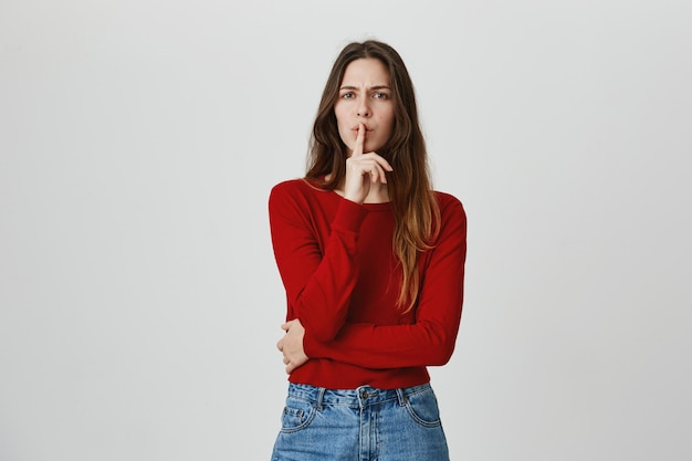 Aantrekkelijk meisje vraagt om geheim te houden, zwijg met de vinger tegen de lippen gedrukt, houd alsjeblieft stil