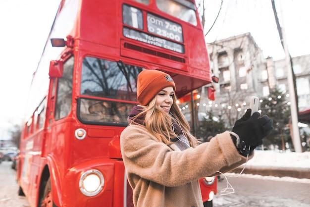 Aantrekkelijk meisje wandelen door de straten van de winter-stad en selfie te nemen