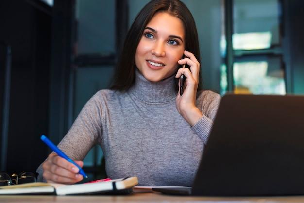 Aantrekkelijk meisje zit aan tafel voor laptop en praat op mobiele telefoon, maakt aantekeningen in notitieblok.