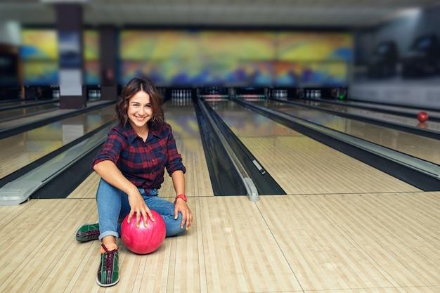 Aantrekkelijk meisje zittend met bal op de vloer in de bowlingclub