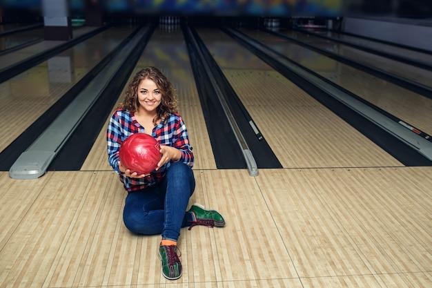 Aantrekkelijk meisje zittend met bal op de vloer in de bowlingclub.