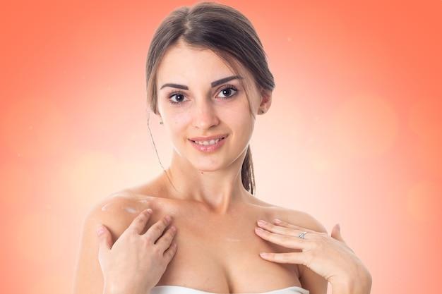 Aantrekkelijk meisje zorgt voor haar huid geïsoleerd op een witte achtergrond. gezondheidszorgconcept. lichaamsverzorgingsconcept. jonge vrouw met een gezonde huid.