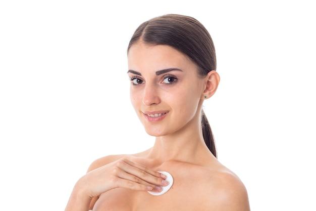 Aantrekkelijk meisje zorgt voor haar huid met reinigings wattenschijfje geïsoleerd op een witte achtergrond. gezondheidszorgconcept. lichaamsverzorgingsconcept. jonge vrouw met een gezonde huid.
