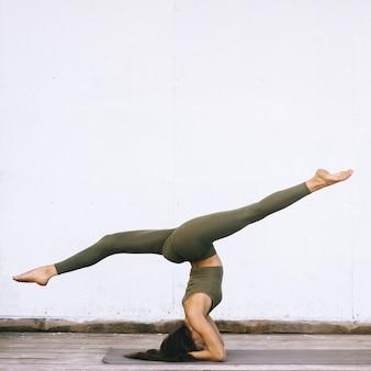 Aantrekkelijk model die yogaoefeningen op witte achtergrond in seksuele kleren doen