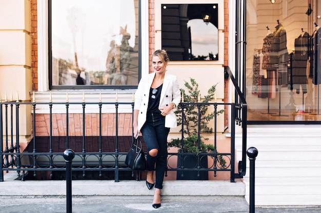 Aantrekkelijk model in wit jasje op hielen leunt op hek op winkel achtergrond. ze houdt haar hand in de zak en lacht naar de camera.