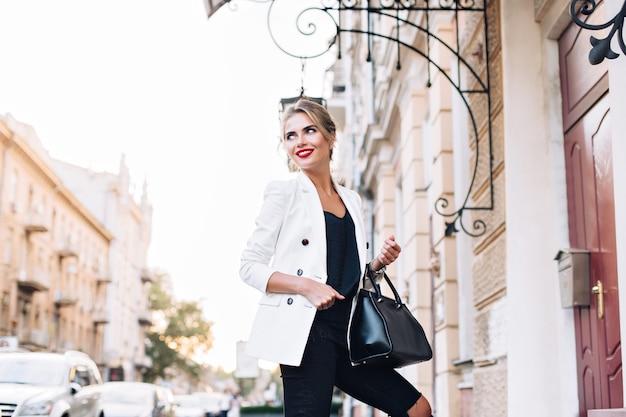 Aantrekkelijk model in witte jas op straat in de stad. ze glimlacht naar haar kant.