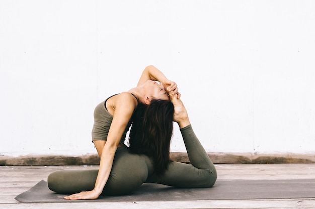 Aantrekkelijk model in yoga pose op wit oppervlak in kleding