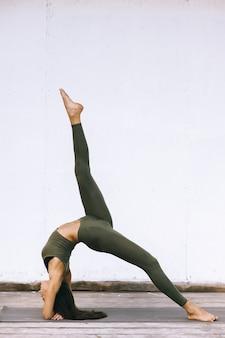 Aantrekkelijk model in yoga stelt op witte achtergrond