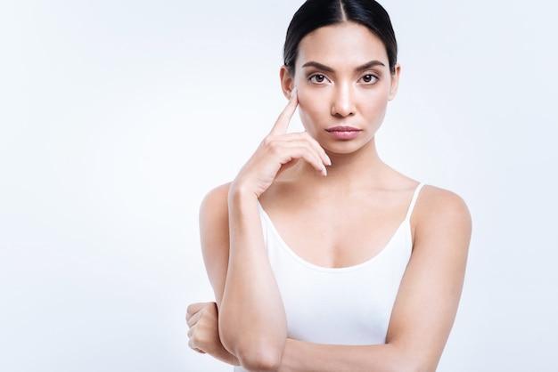 Aantrekkelijk model. mooie donkerharige vrouw in een witte tanktop die haar jukbeen aanraakt met een vinger terwijl ze tegen een witte muur poseert