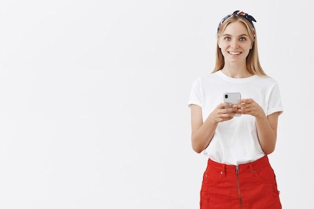 Aantrekkelijk modern meisje met behulp van mobiele telefoon en glimlachen