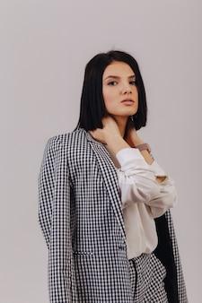 Aantrekkelijk modieus jong meisje in bedrijfskleren die op lichte achtergrond in studio stellen. concept van stijlvolle kleding en verfijning.