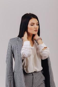 Aantrekkelijk modieus jong meisje in bedrijfskleren die op lichte muur in studio stellen. concept van stijlvolle kleding en verfijning.