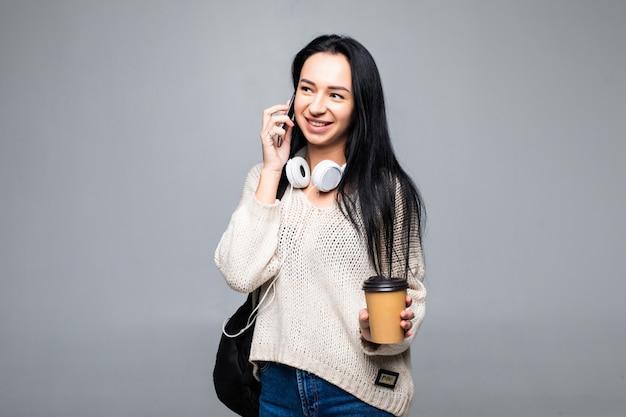 Aantrekkelijk modieus meisje dat vrolijk lacht terwijl het spreken op mobiele telefoon aan haar vriend, geïsoleerd op grijze muur. gesprek concept.