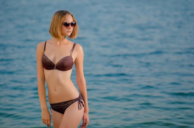 Aantrekkelijk mooi kaukasisch slank meisje in een bril op het strand, staat op azuurblauw water. recreatie en verwennerij aan de kust (oceaan, rivier, meer) bij zonsondergang.