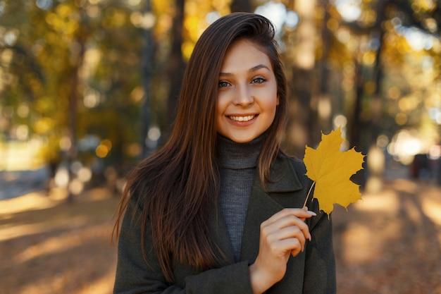 Aantrekkelijk mooi stijlvol gelukkig meisje met een glimlach in een modieuze vintage jas houdt in haar hand een geel herfstblad tijdens een wandeling in het park. mooie vrouw glimlach.