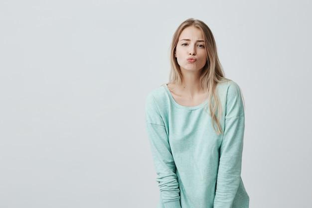 Aantrekkelijk mooi vrouwelijk model met blond haar, pruilt lippen, stuurt kussen