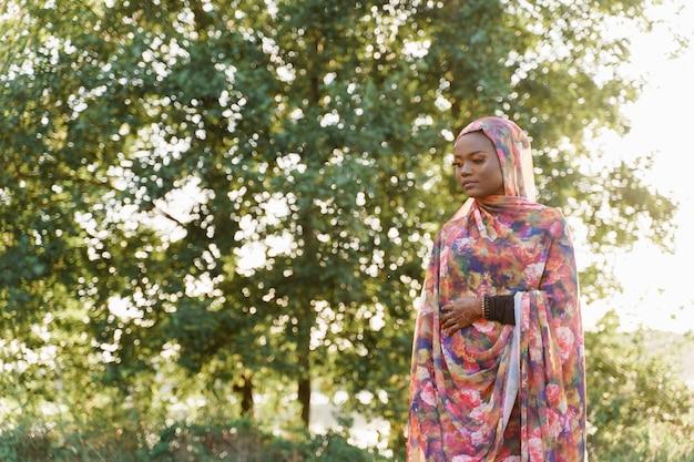 Aantrekkelijk moslim zwart meisje weared in hijab glimlacht en kijkt naar links