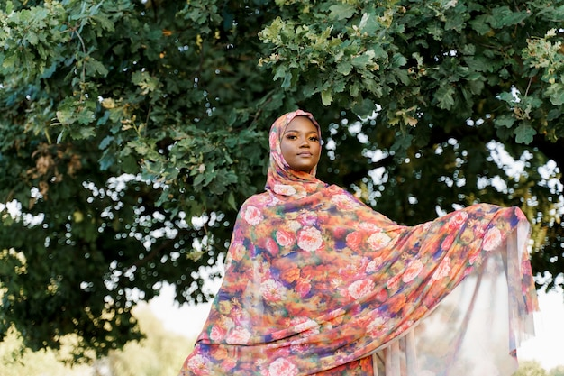 Aantrekkelijk moslim zwart meisje weared in hijab glimlacht in de buurt van groene boom