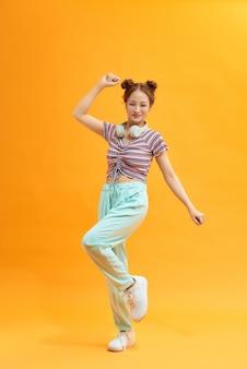 Aantrekkelijk onvoorzichtig vrolijk meisje dat luistert naar bas die plezier heeft geïsoleerd over felgele kleurachtergrond