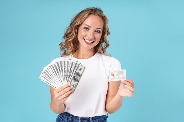 Aantrekkelijk opgewonden jong meisje met casual kleding die geïsoleerd op blauw staat en geldbankbiljetten en creditcard toont