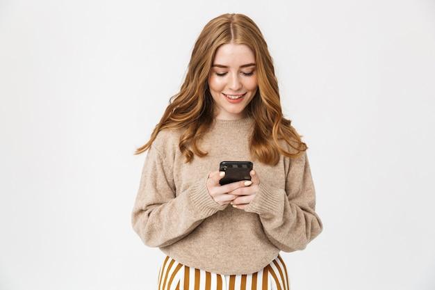 Aantrekkelijk opgewonden jong meisje met een trui die over een witte muur staat en mobiele telefoon gebruikt