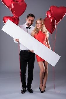Aantrekkelijk paar dat een leeg aanplakbiljet houdt