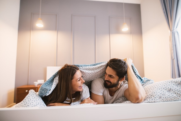 Aantrekkelijk paar dat onder de deken ligt die naar elkaar glimlacht.