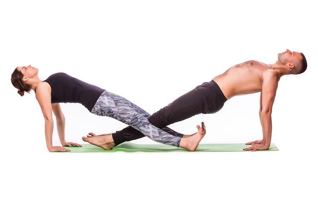 Aantrekkelijk paar dat yoga samen op witte achtergrond doet