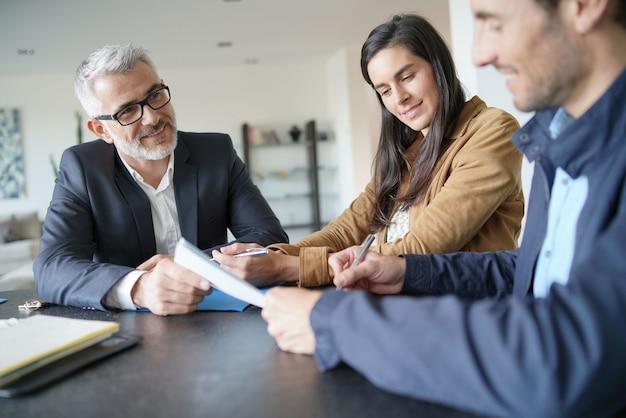 Aantrekkelijk paar die contract met onroerende goederenagent ondertekenen in eigentijds huis