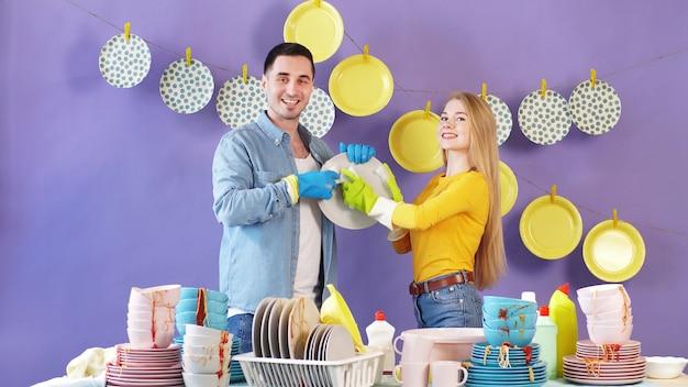 Aantrekkelijk paar die huishoudenkarweien samen doen, afwassen, geïsoleerde achtergrond