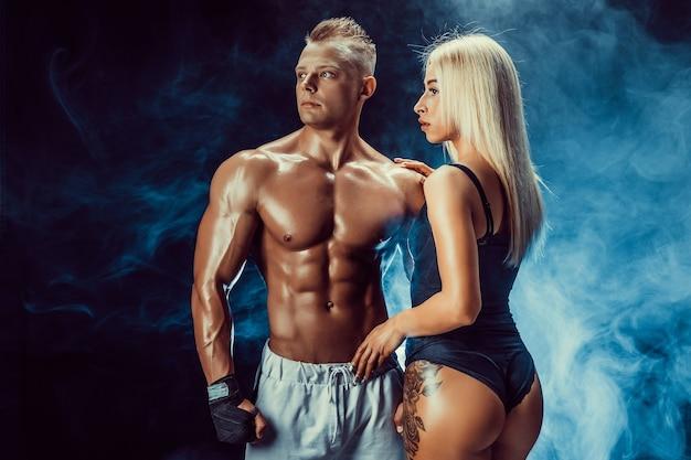 Aantrekkelijk paar, een slanke blonde vrouw en knappe shirtless man poseren in studio op een donkere structuur met rook.