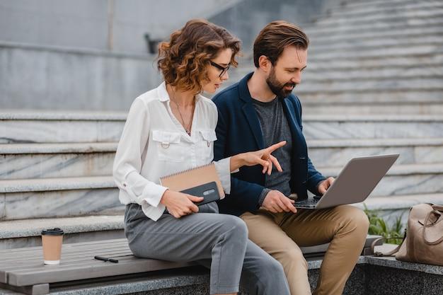 Aantrekkelijk paar man en vrouw praten zittend op trappen in het centrum van de stad, samenwerken op laptop