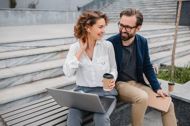 Aantrekkelijk paar man en vrouw zittend op trappen in stedelijk stadscentrum