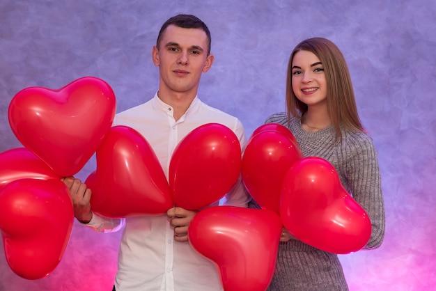 Aantrekkelijk paar met rode luchtballonnen die in studio glimlachen. verliefd stel