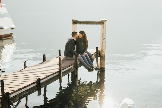 Aantrekkelijk paar op de houten steiger aan een meer van lugano in zwitserland.