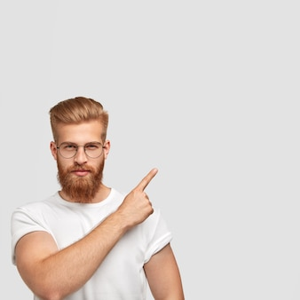 Aantrekkelijk rood mannetje heeft een dikke baard, gekleed in een vrijetijdskleding, heeft een serieuze uitdrukking, wijst met wijsvinger in de rechterbovenhoek