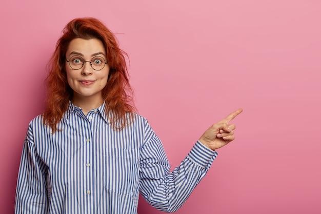 Aantrekkelijk roodharig vrouwelijk model introduceert coole lege ruimte-promo, draagt een ronde bril en een blauw gestreept overhemd