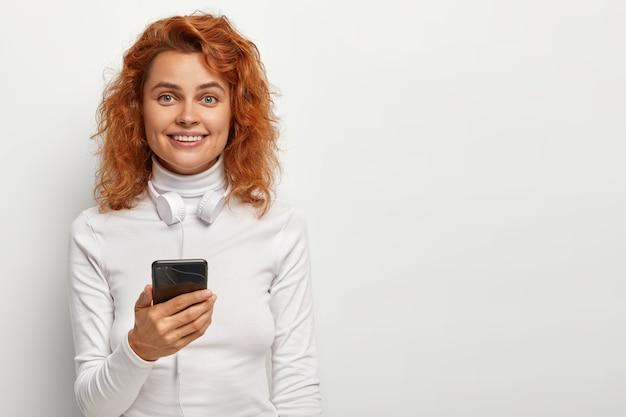 Aantrekkelijk roodharige meisje heeft een tevreden blik, houdt telefoon vast, luistert naar favoriete muziek met een koptelefoon, heeft een charmante glimlach