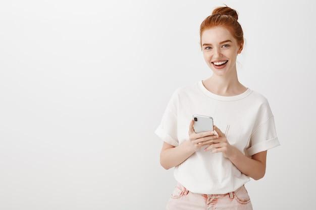 Aantrekkelijk roodharigemeisje met smartphone het glimlachen